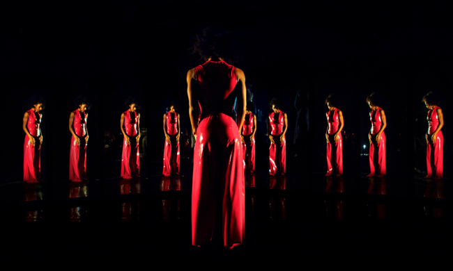 performer in a red dress looking at multiple reflections with herself in a mirror