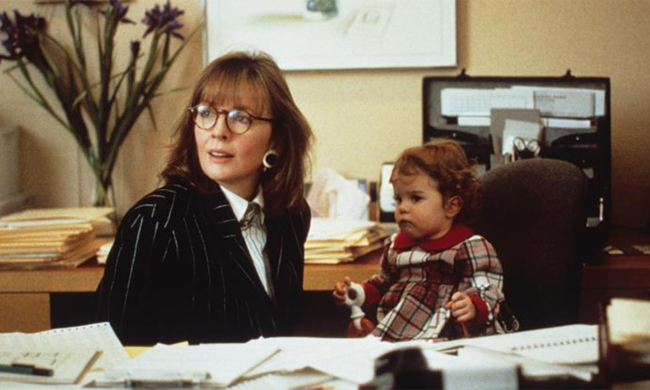 Diane Keaton with a baby in a chair next to her.
