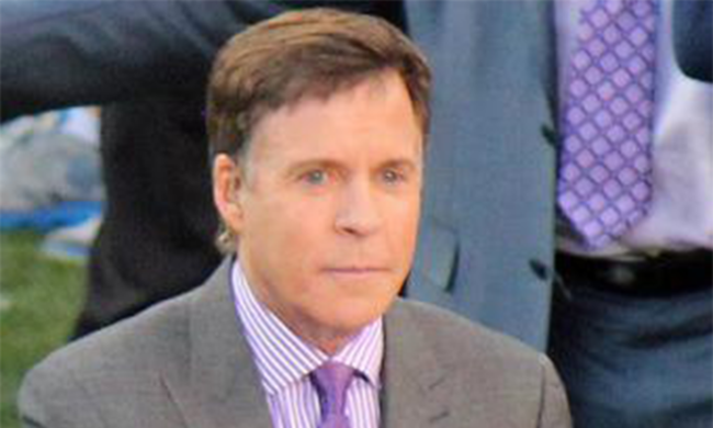 Bob Costas sitting at a table.