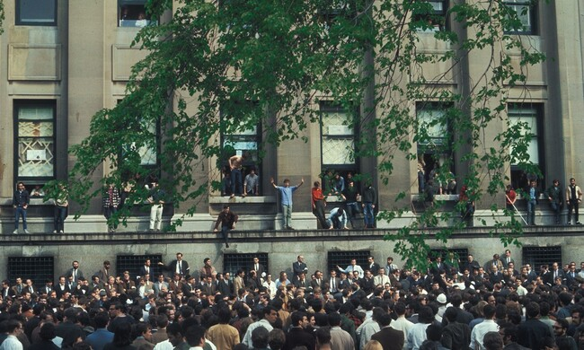 students crowding and surrounding the exterior of an university building