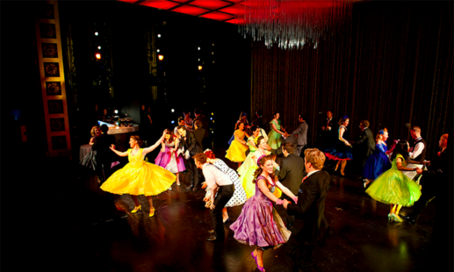 Several people in colorful outfits dance on stage.