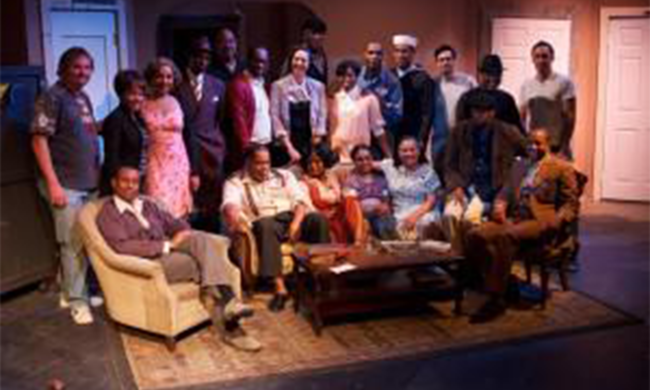 The cast and crew of a play gathered around their set.