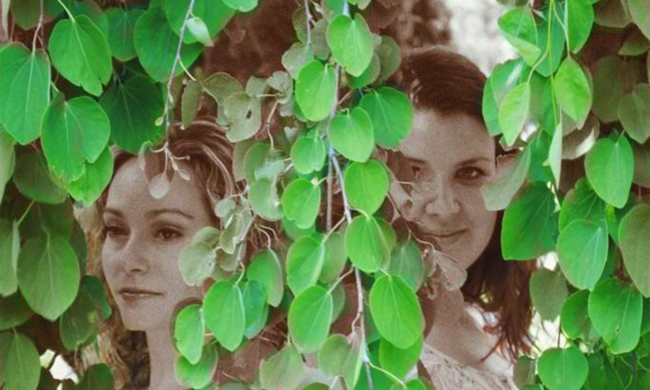 Two women standing among vines.