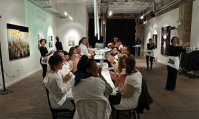 Several people sit at a table in a gallery.