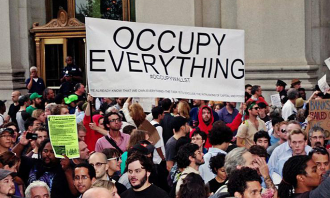 "A large group of people with a sign that reads ""Occupy Everything"" behind them."