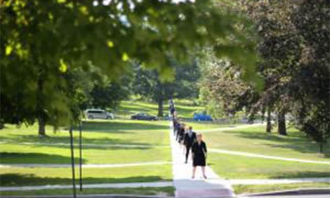 Several people walking in a line down a sidewalk in a park.