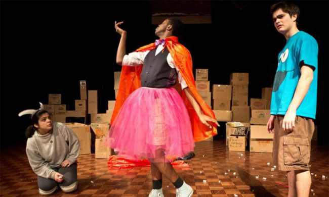 Three people stand on a stage. One kneels on the ground wearing horns, one poses while wearing a pink tutu and orange cape, and other looks out into the audience while wearing a cookie monster t-shirt.
