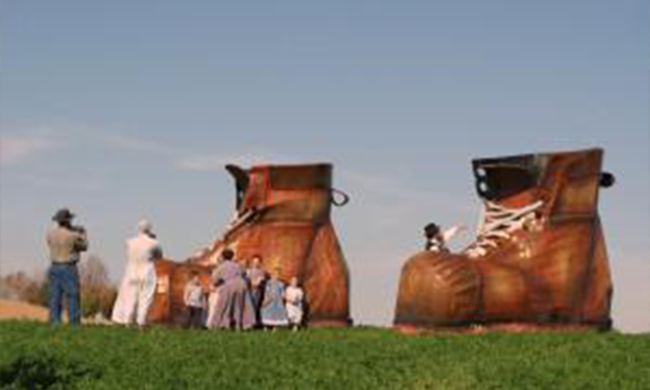 Two giant shoes with people gathered around.