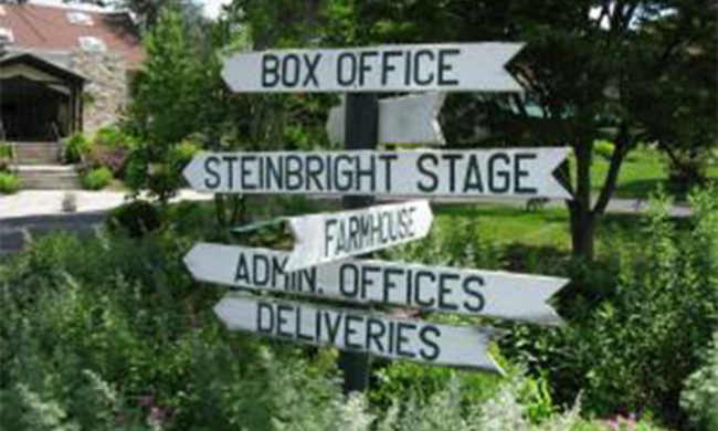 An outdoor sign pointing toward several offices.