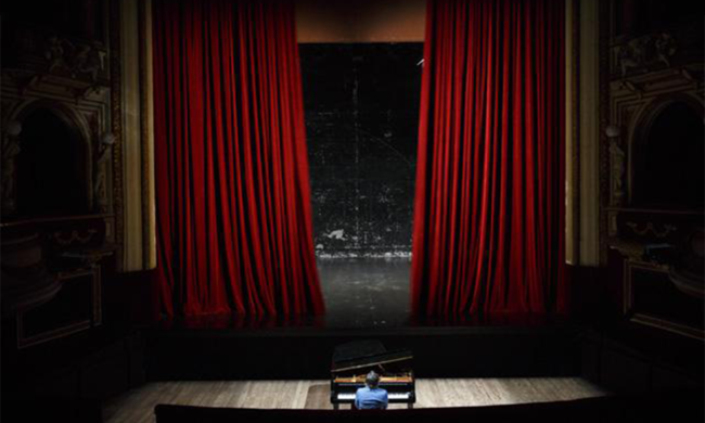 A man sits at a piano in front of a stage.
