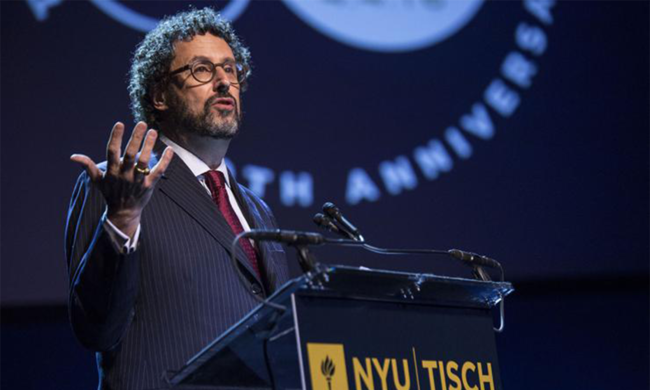 Tony Kushner giving a speech in front of an NYU Tisch podium