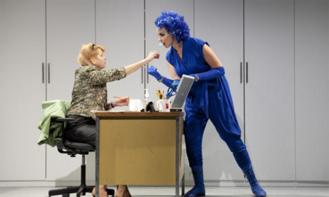 A woman at a desk stretches her hand out to a woman wearing an entirely blue outfit and a blue wig.