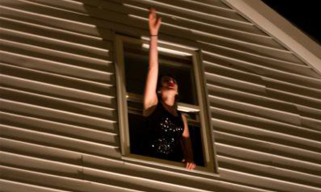 A person waving out of a window.