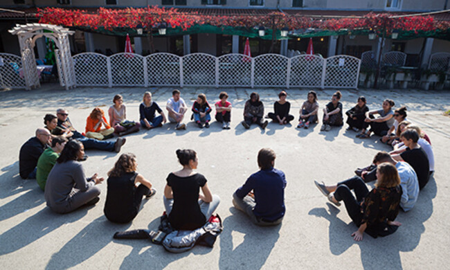 a large group of people sit on the ground in a circle