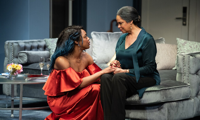 two Black actresses sit on a couch