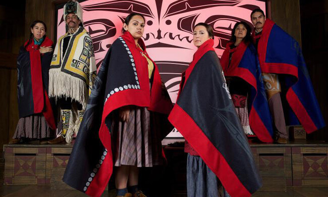 Two native women stand at the center of the photo with their bodies turned toward each other and facing the camera. Their expressions are serious. They are dressed in the cultural wear of their people.