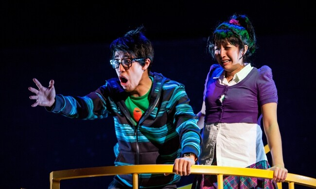 two performers making faces holding a rail