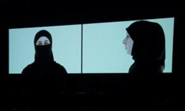 two women projected onto screens