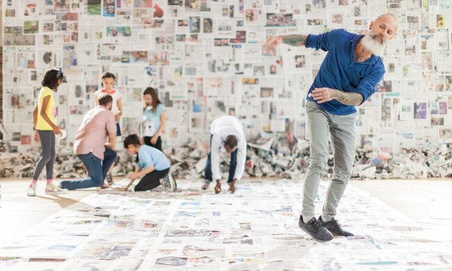 actors in front of a colorful wall of newspaper