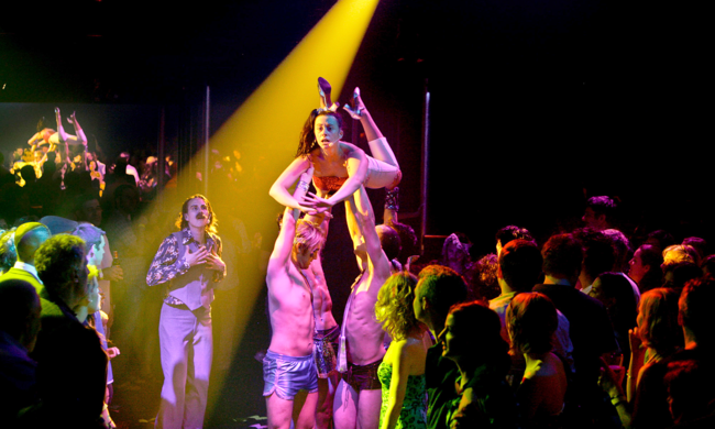 four actors onstage surrounding by an audience standing