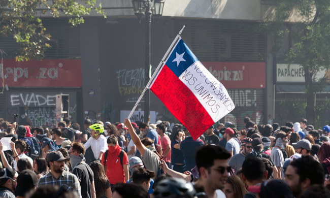 a large group of protesters with a Chilean flag