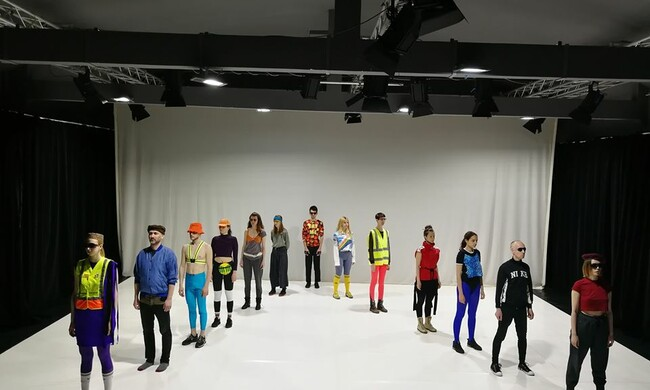 "several performers standing in a ""V"" formation dressed in colorful techno dance clothes."