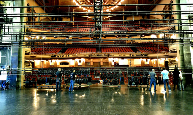 a backstage crew in the process of hanging lights in a theatre