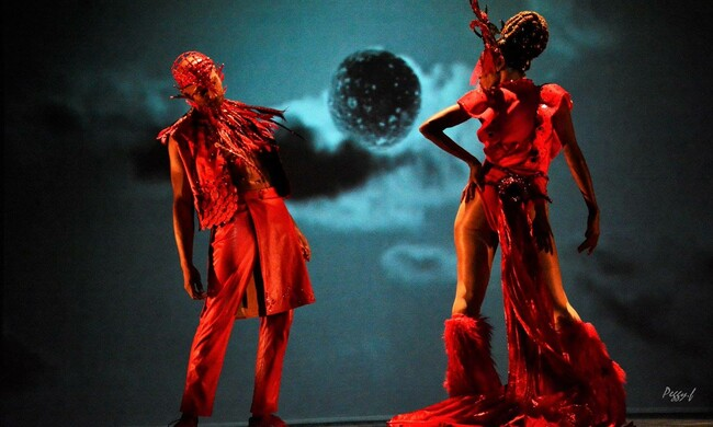 two performers in red costumes with a backdrop of the moon.