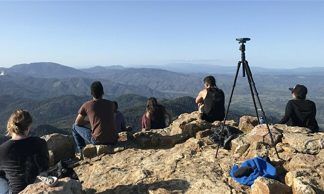 people sitting on a mountain facing away from camera with tripod in foreground