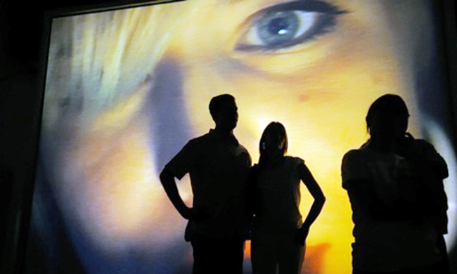 three people looking at a large projection of a person's face
