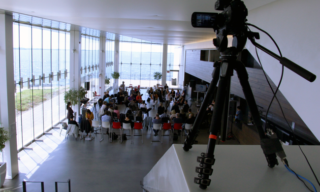 balcony view of a large group sitting in two concentric circles