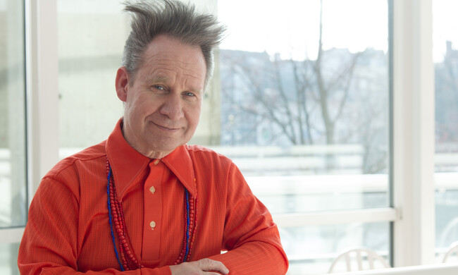 Peter Sellars in a red shirt next to a window.