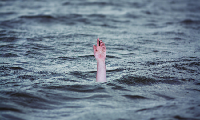 a lightskinned hand reaching up out of water