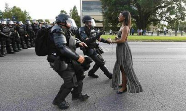 black woman in dress stands with arms out in front of uniformed police officers
