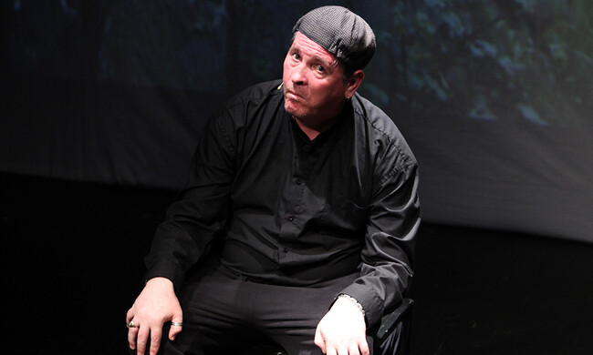 performer sitting, wearing a black button-down and black pants.