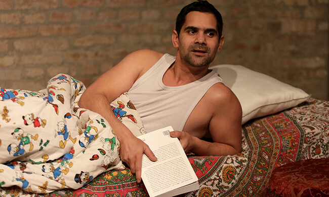 person in a bed, holding a book.
