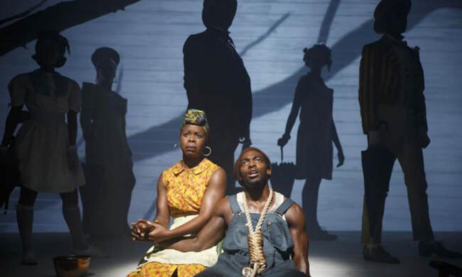 two actors onstage with five actors' shadows behind them