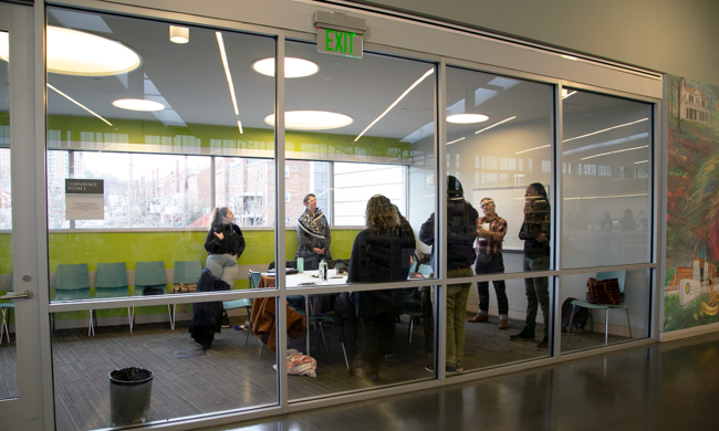 view from a hallway of a group standing and talking in a conference room