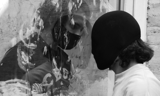 black and white photo of two people in different masks facing each other through glass