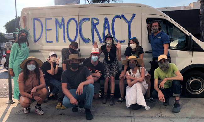 "a group posing for a photo in front of a white van with ""democracy"" written on it"