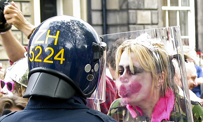 a clown kissing a clear riot shield