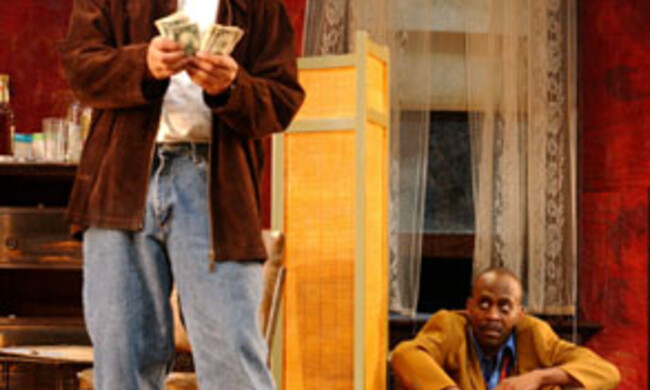 One actor counts money, the other sits on the floor looking
