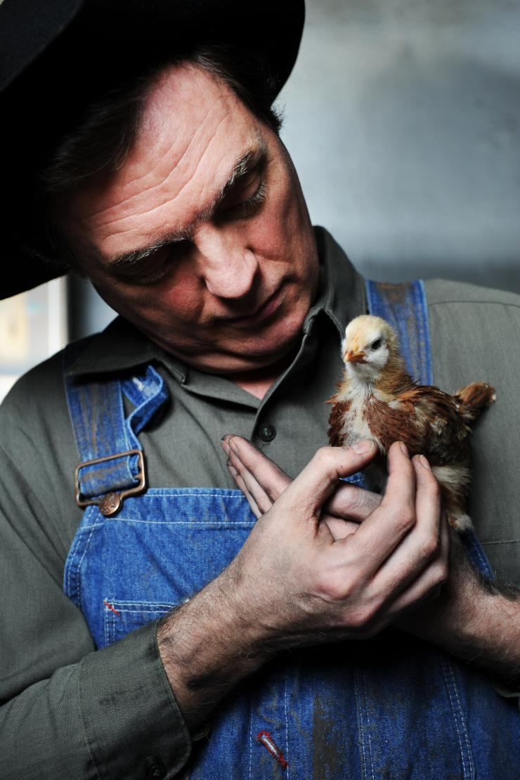 a man holding a baby chick.