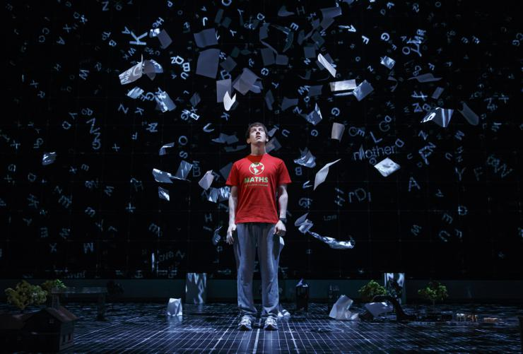 actor on stage surrounded by paper