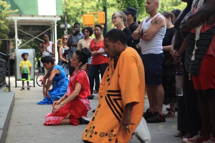 three performers kneel outside with an audience standing behind them