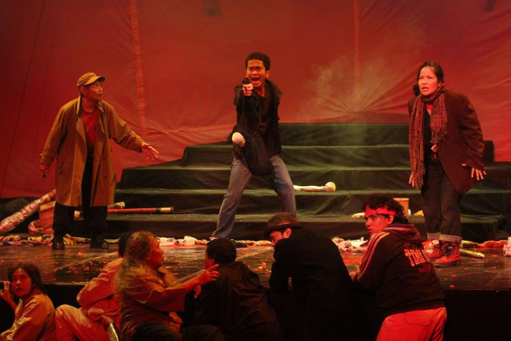actors standing and crouching on a red stage, performing concern