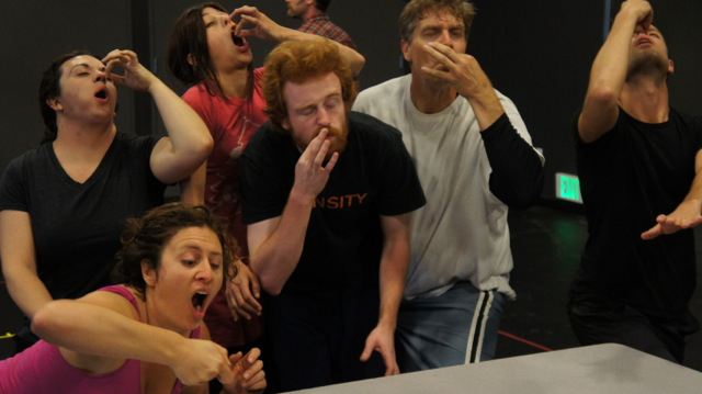 a group of actors miming eating