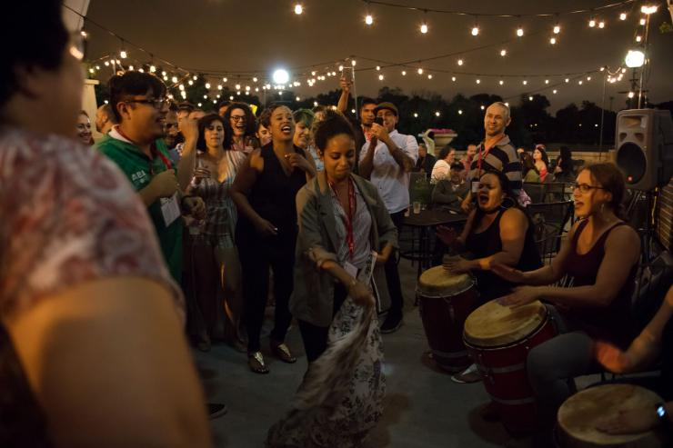 A woman dances in a circle of people as other women play drums