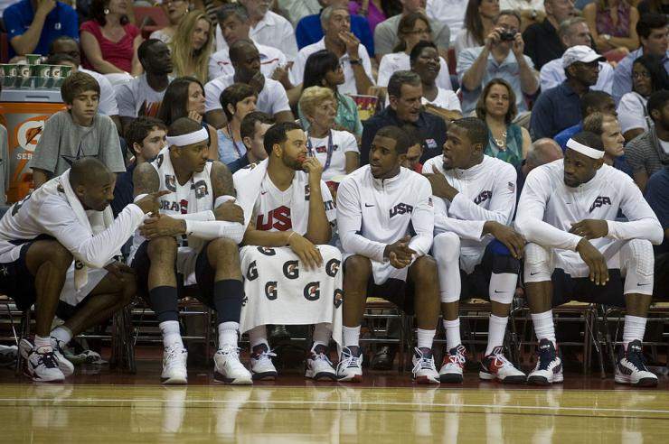 Six basketball players sitting on the bench