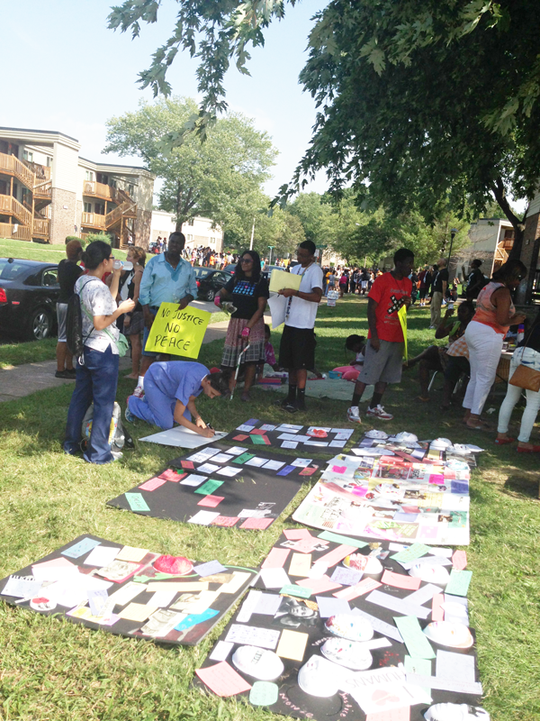 People making protest signs at a park